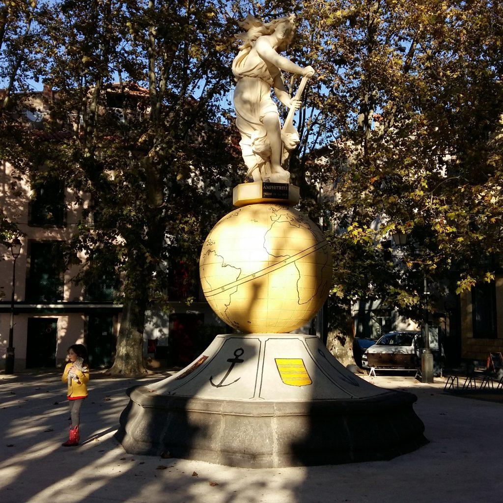 enfant devant une sculpture dans le centre historique d'Agde
