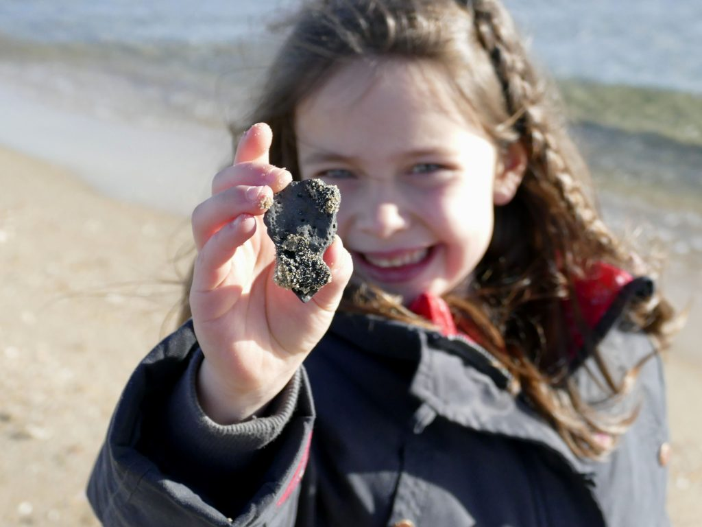 enfant qui montre une pierre de lave ramassée au Cap d'Agde