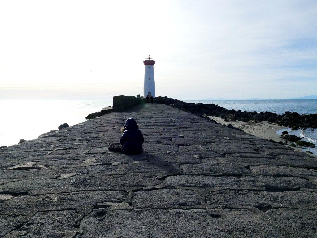 enfant qui boude devant le phare de la Tamarissière