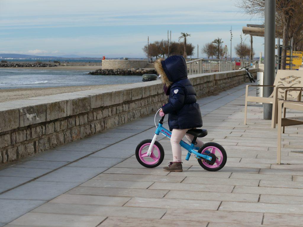 Enfant sur une draisienne sur la promenade du Grau d'Agde