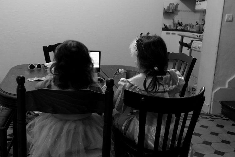 enfants déguisées regardant un lecteur dvd en mangeant