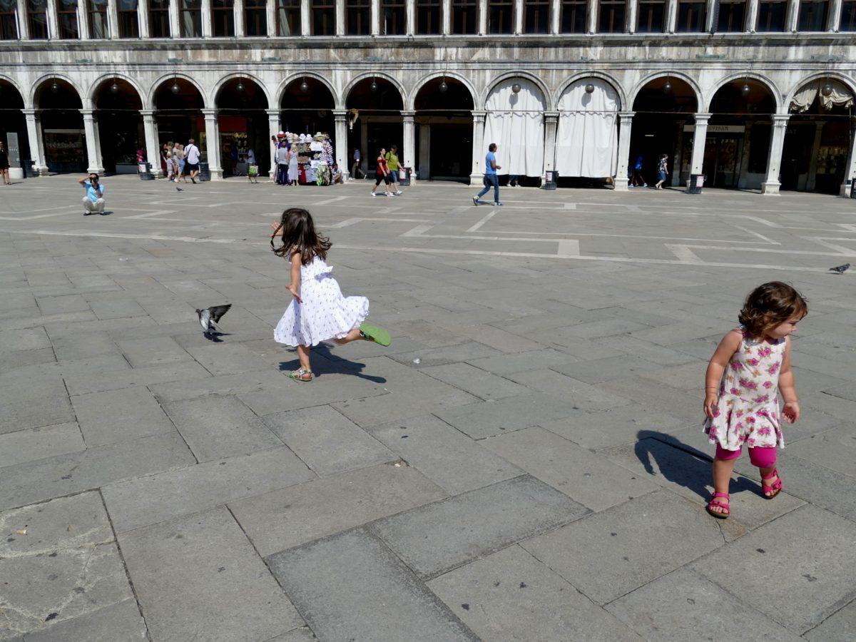 enfant courant après les pigeons sur la place San Marco
