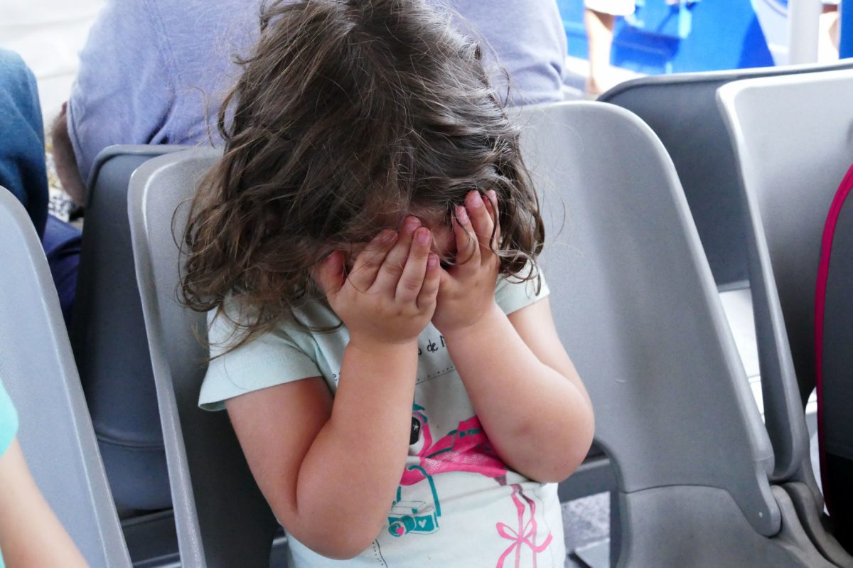 enfant se cachant le visage