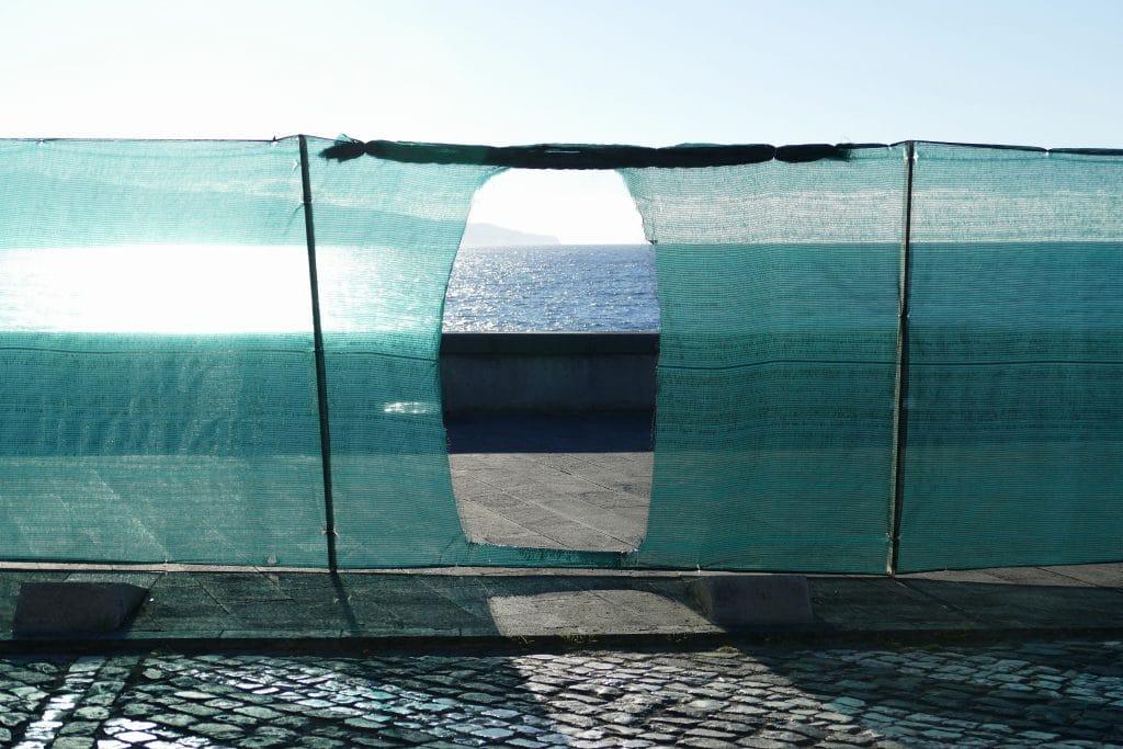 Passage dans une palissade donnant sur la mer